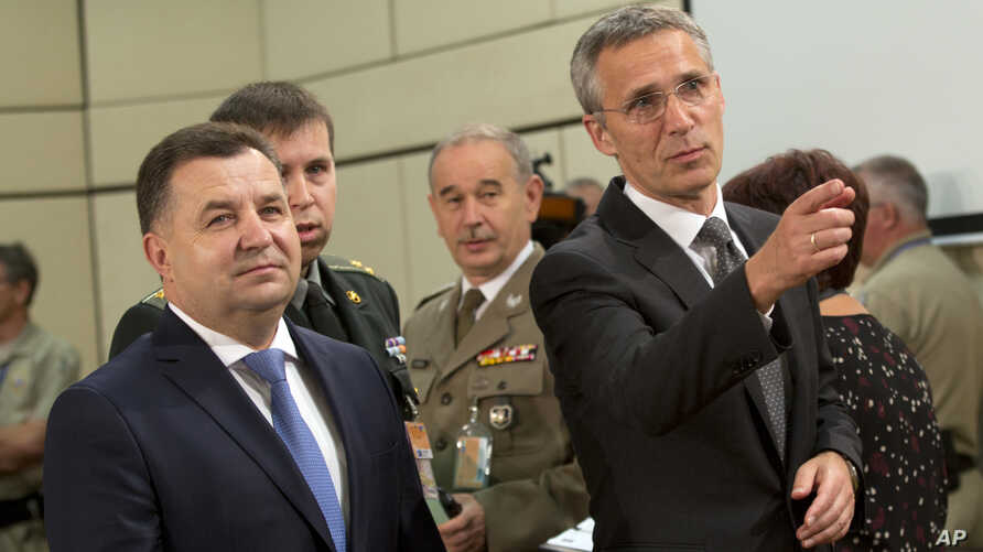 NATO Secretary General Jens Stoltenberg, right, and Ukraine's Defense Minister Stepan Poltorak, left, arrive for a meeting of the NATO-Ukraine Commission at NATO headquarters in Brussels, June 25, 2015.
