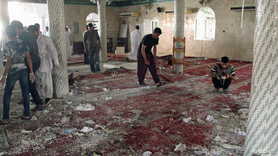People examine the debris after a suicide bomb attack at the Imam Ali mosque in the village of al-Qadeeh in the eastern province of Gatif, Saudi Arabia, May 22, 2015.