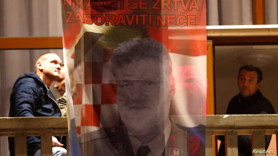 """Bosnian Croats hang a flag displaying a portrait of General Slobodan Praljak and a message that reads, """"Your sacrifice will never be forgotten,"""" as people pray and light candles for the convicted general, who killed himself seconds after a judge at a"""