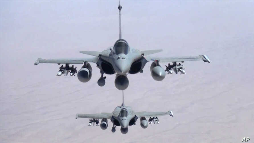 This remote camera screen grab photo provided Friday, Sept.19, 2014 by the French Army's video and photo department ECPAD shows two Rafale jet fighters fly over Iraq Friday.