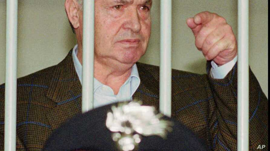 """FILE - Mafia """"boss of bosses"""" Salvatore """"Toto"""" Riina is seen behind bars during a trial in Rome, April 29, 1993. Riina has died while serving multiple life sentences. He was 87."""