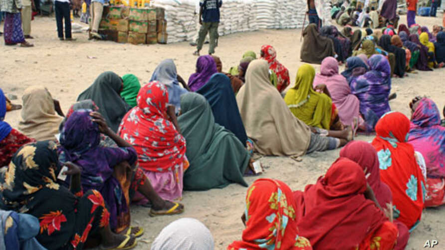 Internally displaced Somali women queue to receive food-aid rations at a distribution center in a displaced persons camp in the Somali capital Mogadishu, on July 26, 2011