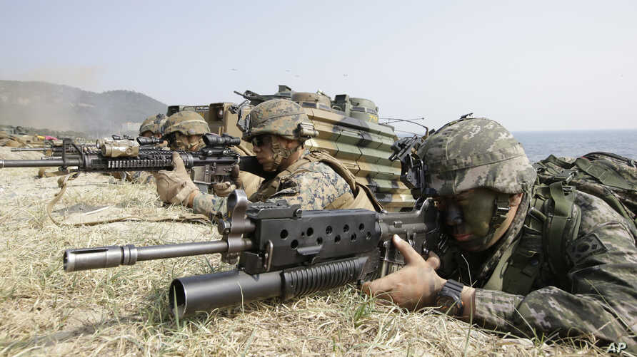 FILE – A South Korean Marine, right, and U.S. Marines aim