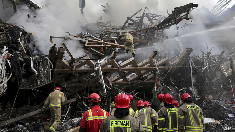 Iranian firefighters remove debris of the Plasco building which was engulfed by a fire and collapsed on Thursday, in central Tehran, Iran, Jan. 20, 2017.