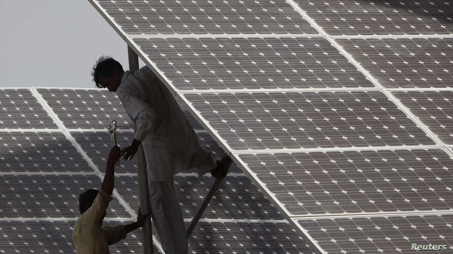 Technicians work on solar panel in power station at Hub about 25 km (15 miles) from Karachi, Pakistan, June 18, 2010.