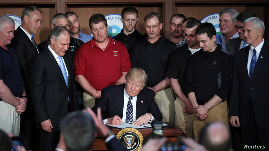 US President Donald Trump reacts after signing an executive order eliminating Obama-era climate change regulations at the Environmental Protection Agency in Washington, March 28, 2017.