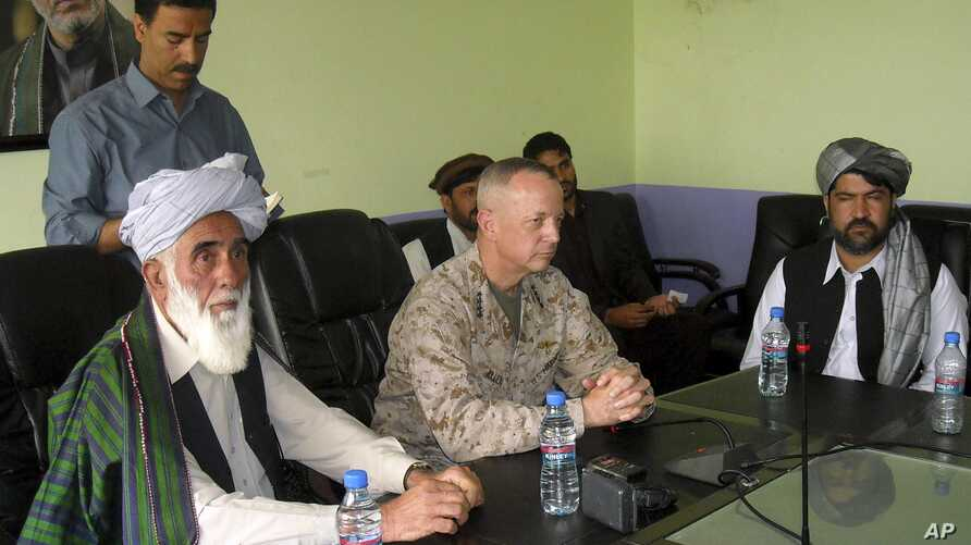The commander of U.S. and NATO troops in Afghanistan, General John Allen, center, meets with the Governor of Logar Province, Allhaj Mohammad Tahir Sabari, left, south of Kabul, Afghanistan, June 8, 2012.