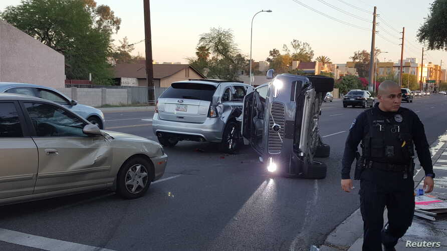 A self-driven Volvo SUV owned and operated by Uber Technologies Inc. is flipped on its side after a collision in Tempe, Ariz., March 24, 2017.