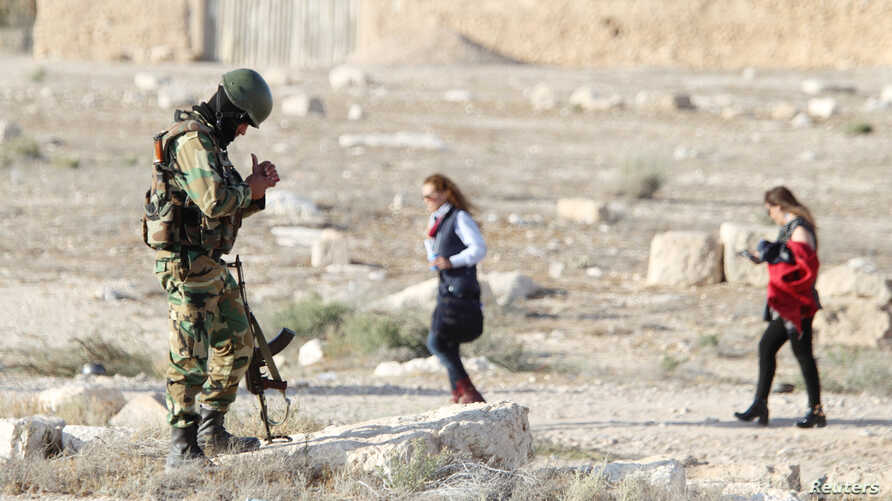 file - A Syrian army soldier looks at his mobile as people visit the ruins of the historic city of Palmyra ahead of a musical event at its amphitheater, Syria, May 6, 2016.