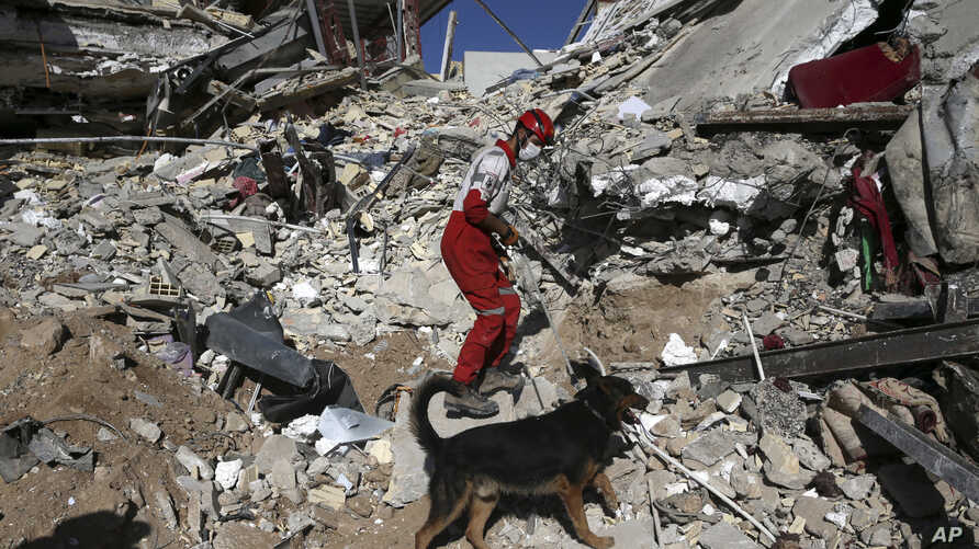 A rescue worker searches the debris with his sniffing dog on the earthquake site in Sarpol-e-Zahab in western Iran, Nov. 14, 2017.