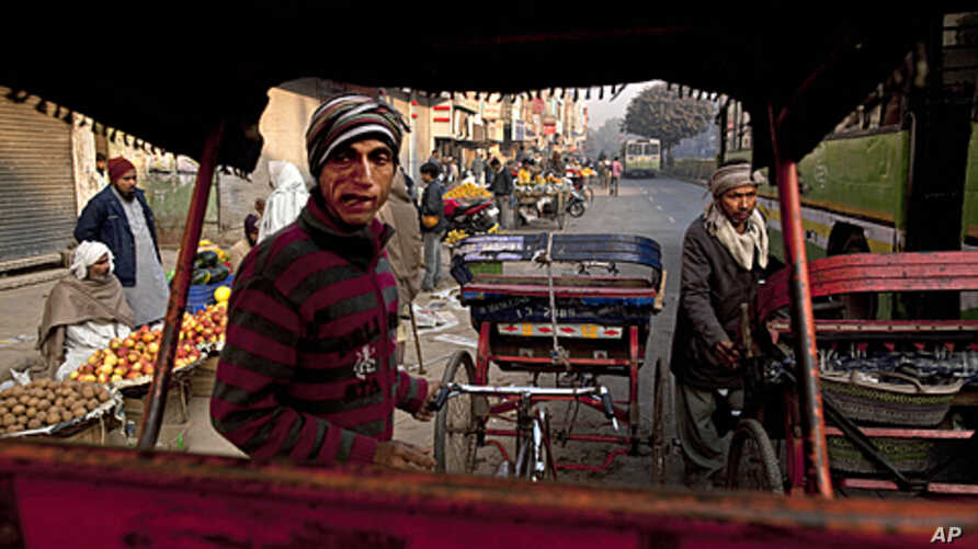 Indian rickshaw drivers wait for passengers as vendors sell fruit and vegetables at a street market in New Delhi, India, December 15, 2011.