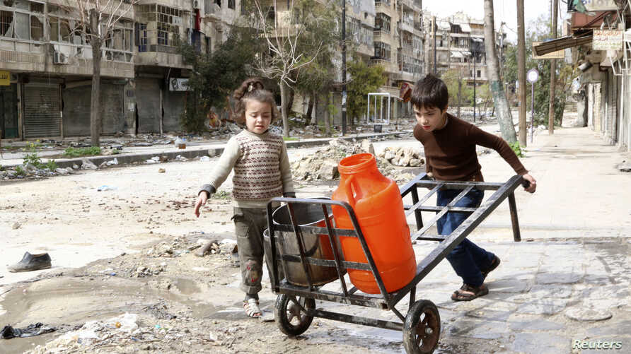 Children push a cart with water containers along a damaged street in old Aleppo March 11, 2014. The number of children affected by the civil war in Syria has more than doubled over the past year, with hundreds of thousands of young Syrians trapped in