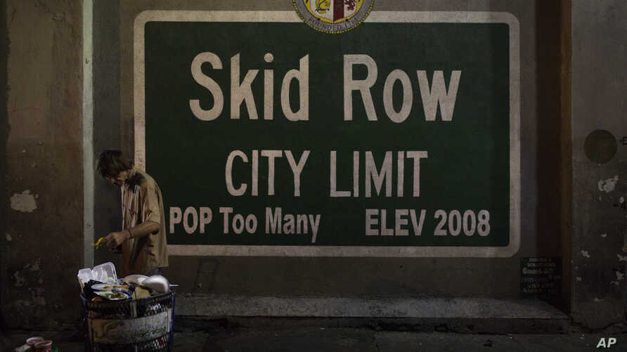 A homeless man takes food from a trash can in Los Angeles' Skid Row area, home to the nation's largest concentration of homeless people, Oct. 28, 2017, in Los Angeles. California declared a statewide emergency because of a hepatitis A outbreak linked