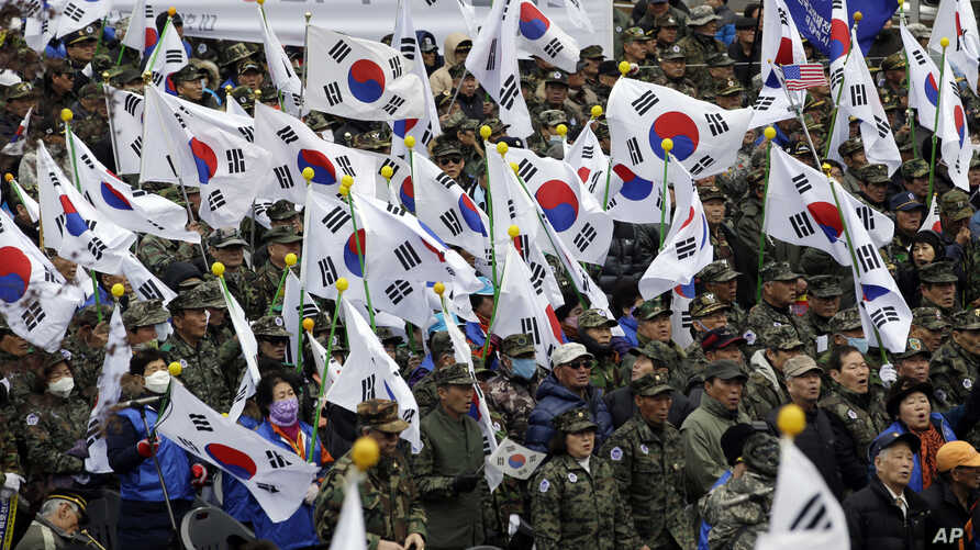 FILE - War veterans and members of conservative groups hold their national flags during a rally to call for unity between two Koreas, in Seoul, South Korea, March 1, 2015.