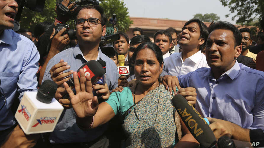 Journalists crowd around Asha Devi, mother of the victim of the fatal 2012 gang rape on a moving bus, after the Supreme Court verdict in the case, in New Delhi, India, May 5, 2017.
