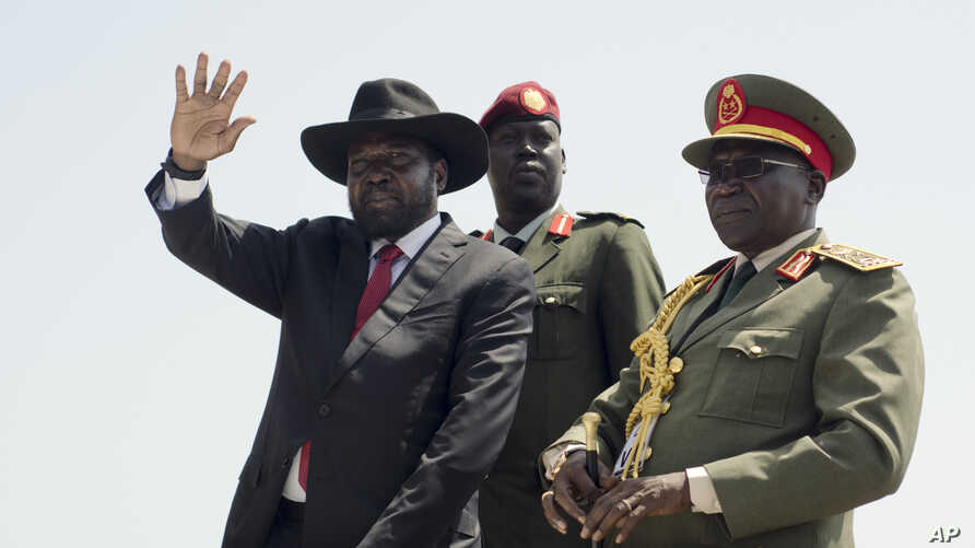 FILE - South Sudan's President Salva Kiir, left, accompanied by army chief of staff Paul Malong Awan, waves during an independence day ceremony in the capital Juba, South Sudan, July 9, 2015.