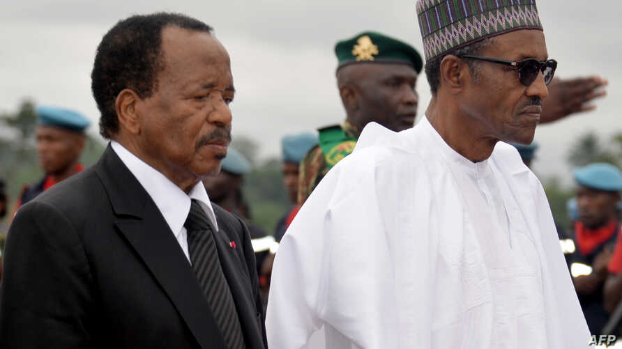 President of Cameroon Paul Biya, left, walks with his Nigerian counterpart, Muhammadu Buhari, following his arrival at the airport in Yaounde, July 29, 2015.