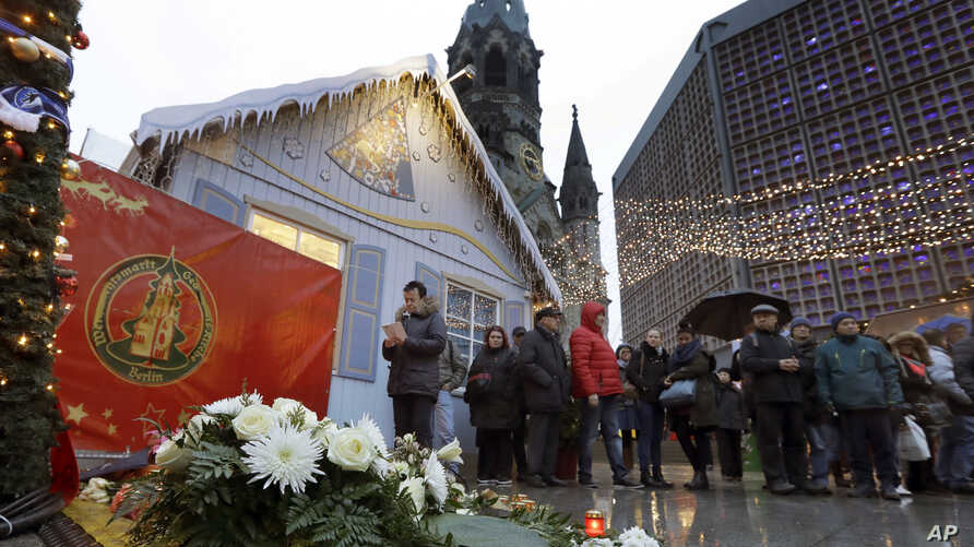A man takes a picture of candles and flowers after the reopening of the Christmas market at the Kaiser Wilhelm Memorial Church in Berlin, Germany, Dec. 22, 2016, three days after a truck ran into the crowded market and killed several people.