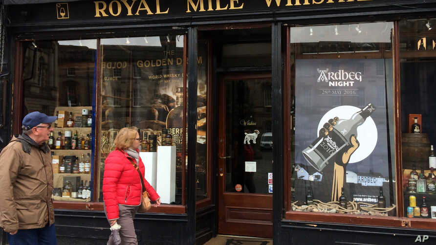 FILE  A man and a woman pass a whisky shop on the 'Royal mile' in Edinburgh, Scotland.