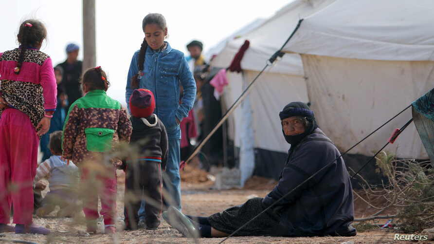 Iraqi refugees rest near tents in an Iraqi refugee camp in the village of Mabrouka, western countryside of Ras al-Ain, Syria, Jan. 31, 2016.