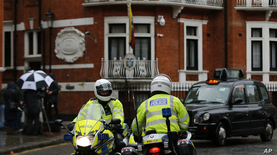 Police motorcyclists briefly stop outside the Ecuadorian embassy in London,  Feb. 13, 2018.