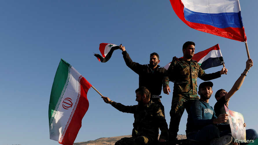Syrians wave Iranian, Russian and Syrian flags during a protest against U.S.-led air strikes in Damascus, Syria, April 14, 2018.