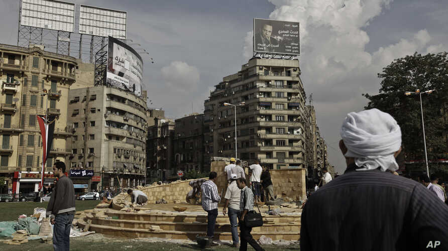 In this Sunday, Nov. 17, 2013 photo, an Egyptian man looks at municipality laborers working on a memorial base two days before the commemoration of deadly clashes with security forces in 2011, in Tahrir Square, Cairo.