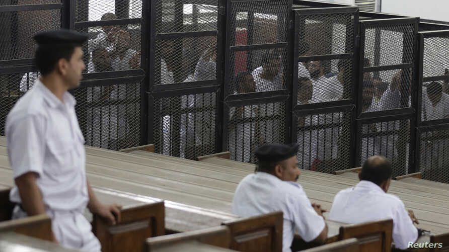 """FILE - Islamist defendants stand behind bars in the case known as the """"Kerdasa massacre'', that referred 188 people to court over an attack that killed 14 policemen in 2013, in Cairo June 23, 2014."""