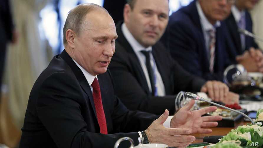 Russian President Vladimir Putin, foreground,  speaks at his meeting with heads of international news agencies at the St. Petersburg International Economic Forum in St. Petersburg, Russia, June 1, 2017.