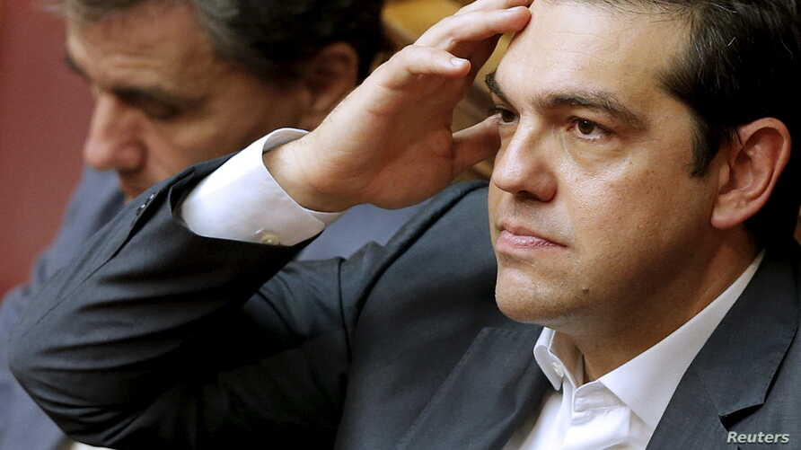 Greek Prime Minister Alexis Tsipras, right, reacts as he sits next to Finance Minister Euclid Tsakalotos during a parliamentary session in Athens, Greece, July 15, 2015.