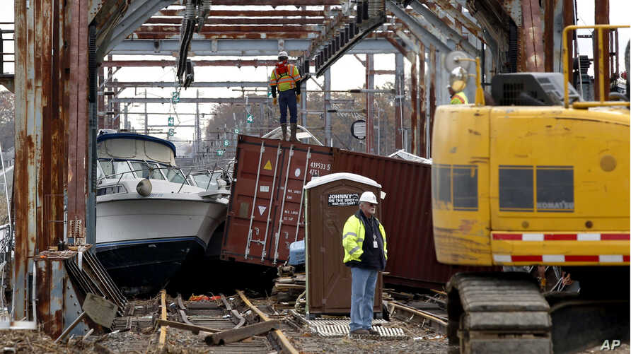 Workers try to clear boats and debris from the New Jersey Transit Morgan draw bridge in South Amboy, New Jersey after Monday's storm surge from Sandy pushed boats and cargo containers onto the train tracks, October 31, 2012.