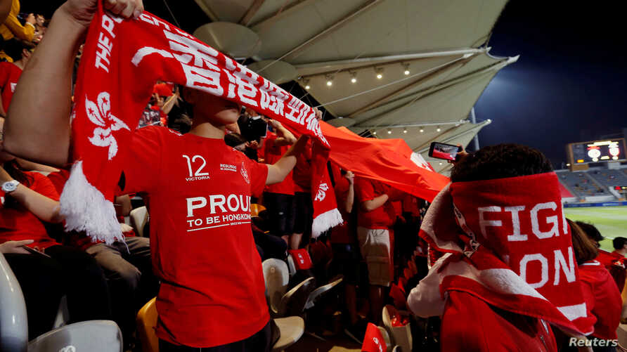 FILE - Hong Kong fans cover their faces and boo during the Chinese national anthem, at a friendly soccer match between Hong Kong and Bahrain in Hong Kong, Nov. 9, 2017.