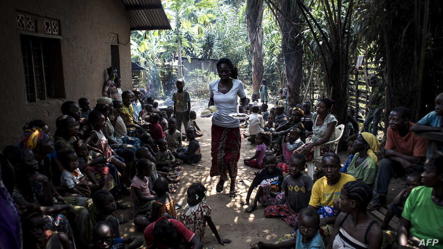 FILE - A volunteer brings daily food rations for Internally Displaced Persons (IDPs), at a camp for IDPs fleeing the conflict in Congo's Kasai province, in Kikwit, DRC, June 7, 2017.