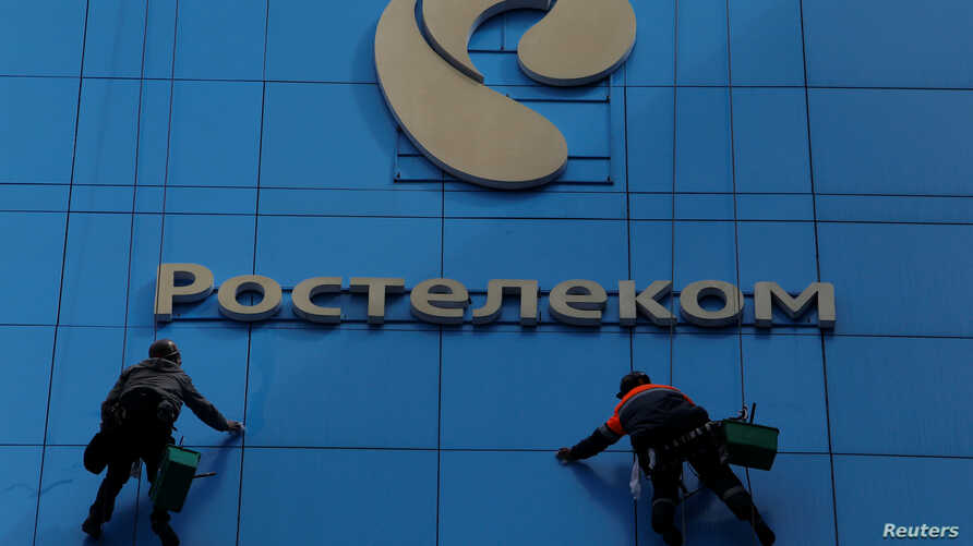 Workers wash the windows of an office building with the logo of Russia's telecom operator Rostelecom, in Moscow, Russia, May 7, 2017.