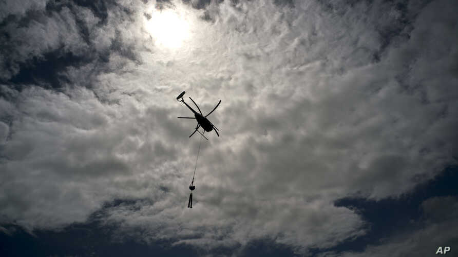A helicopter from Whitefish Energy Holdings flies to power line towers for repairs after the passing of Hurricane Maria in Barceloneta, Puerto Rico, Oct. 15, 2017.