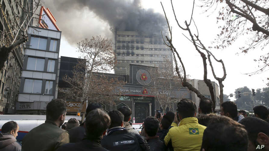 Iranians watch the Plasco building, with smoke rising from its windows, in central Tehran, Iran, Jan. 19, 2017. The high-rise building engulfed by a fire collapsed Thursday as scores of firefighters battled the blaze.