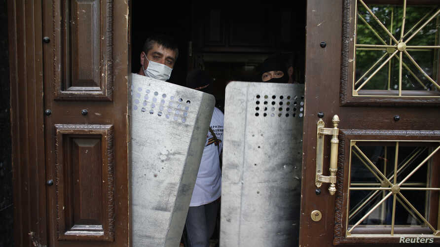 After storming the prosecutor's office, pro-Russia activists stand guard with officers' shields at the entrance in Donetsk, Ukraine, May 1, 2014.