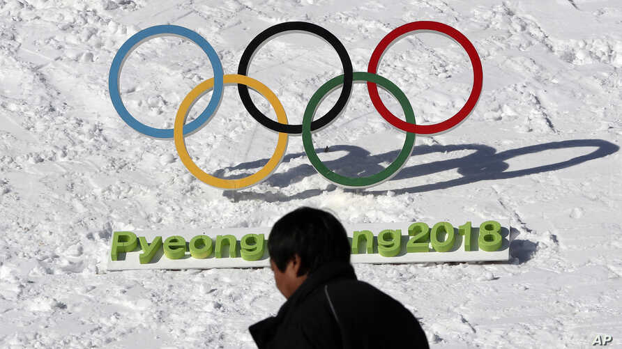 FILE - A man walks by the Olympic rings with a sign of 2018 Pyeongchang Olympic Winter Games, in Pyeongchang, South Korea, Feb. 3, 2017.