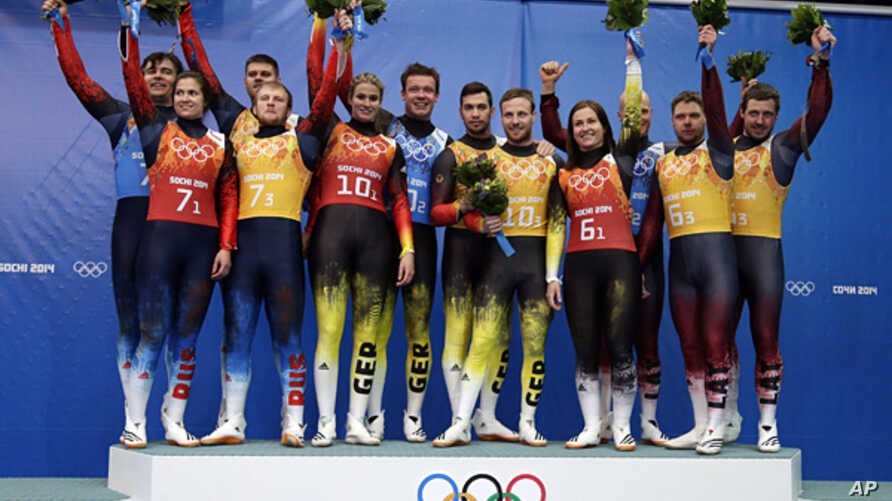 The silver medal team from Russia, (l) gold medal team from Germany, center, and bronze medal team from Latvia (r) pose with flowers after the luge team relay competition at the 2014 Winter Olympics, Feb. 13, 2014, in Krasnaya Polyana, Russia.
