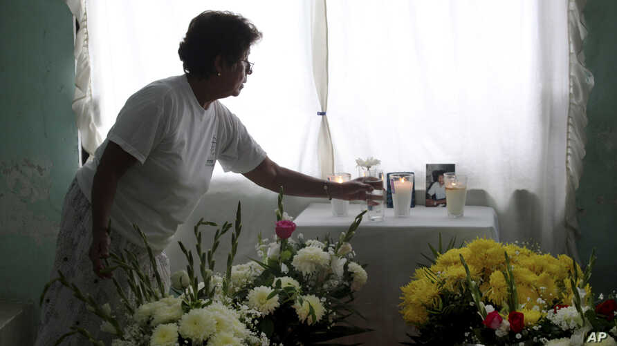 Woman arranges altar at the home of journalist Juan Mendoza Delgado as relatives wait for the arrival of the coffin containing his remains, Medellin, state of Veracruz, Mexico, July 3, 2015.