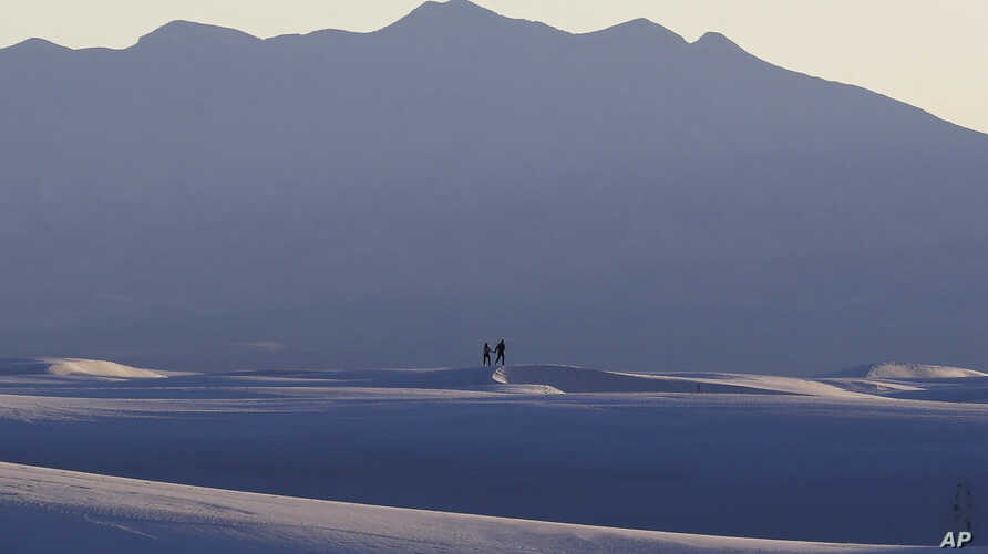 FILE - Visitors walk on sand dunes as the sun sets, March 5, 2015, in White Sands National Monument, New Mexico.