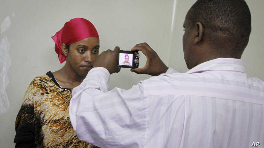 A detained Somali woman has her photograph taken before being fingerprinted and screened at the Kasarani sports stadium, which has been converted into a detention facility to hold those arrested during recent security crackdowns, near Nairobi in Keny