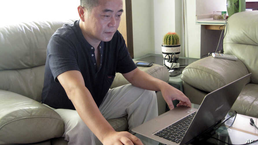FILE - In this Sept. 18, 2012, file photo, veteran rights activist Huang Qi works on his laptop in his home in Chengdu in southwestern China's Sichuan province.