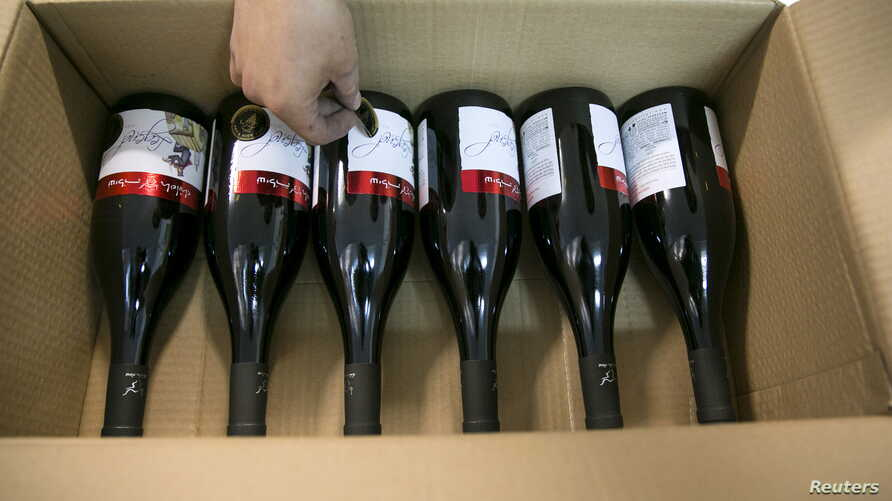 A worker places stickers on wine bottles while packaging them for export at Shiloh Wineries, north of the West Bank city of Ramallah November 8, 2015