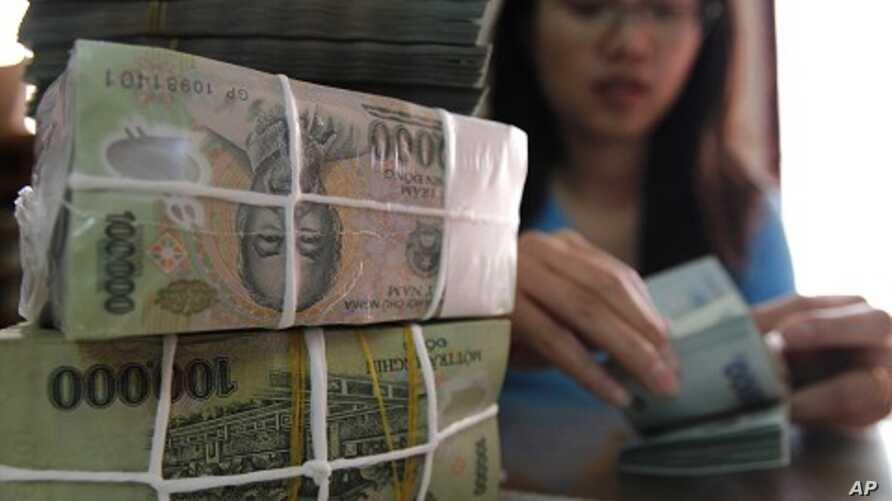 A woman counts Vietnamese dong bank notes in the office of a local company in Hanoi (File)