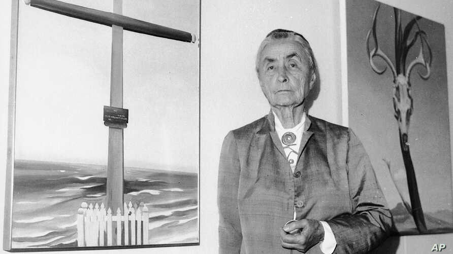 FILE - In this Oct. 8, 1970 file photo, Georgia O'Keeffe stands next to her oil paintings during a press review of 121 paintings, watercolors, and drawings on exhibit at the Whitney Museum of American Art in New York.