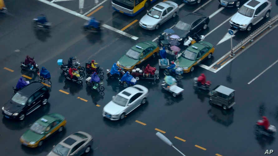 People on electric bikes cross a busy traffic intersection on a rainy day on Chang'an Avenue in Beijing, China Tuesday, Sept. 2, 2014.