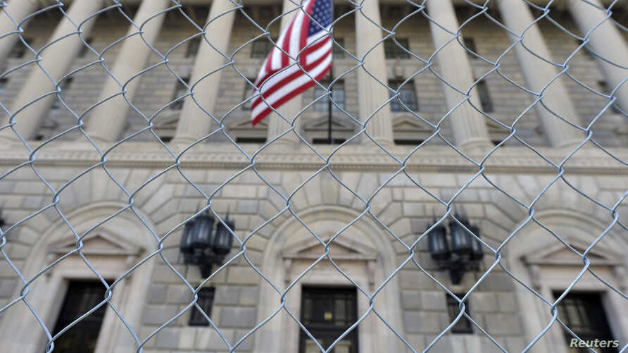 A fence surrounds the U.S. Department of Commerce in Washington October 5, 2013, as the government shutdown continues into the weekend. Washington entered the fifth day of a partial government shutdown on Saturday with no end in sight even as another