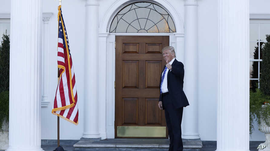 President-elect Donald Trump gives the thumbs-up after Mitt Romney leaves Trump National Golf Club Bedminster in Bedminster, N.J., Nov. 19, 2016.