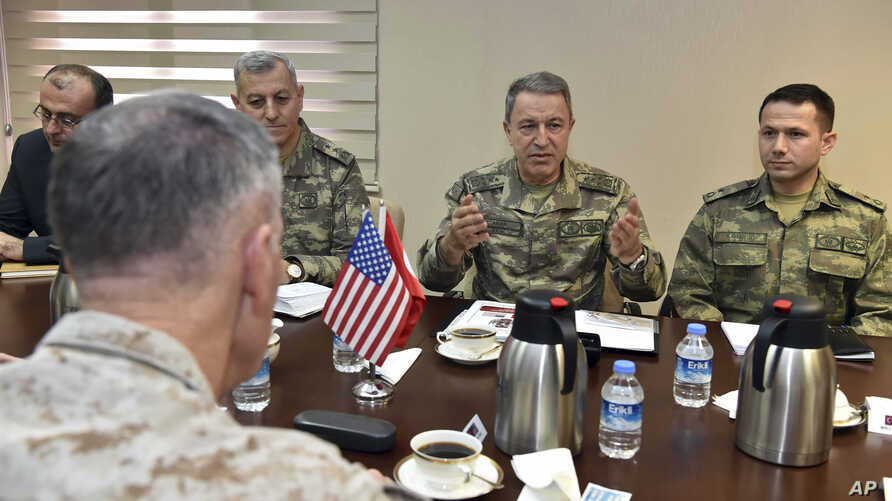 FILE - The U.S. chairman of the Joint Chiefs of Staff, Gen. Joseph Dunford, (back to camera), and Turkey's Chief of Staff Gen. Hulusi Akar (2nd R) talk during a meeting in Incirlik Airbase in Adana, Turkey, Feb. 17, 2017, about the need to fight terr
